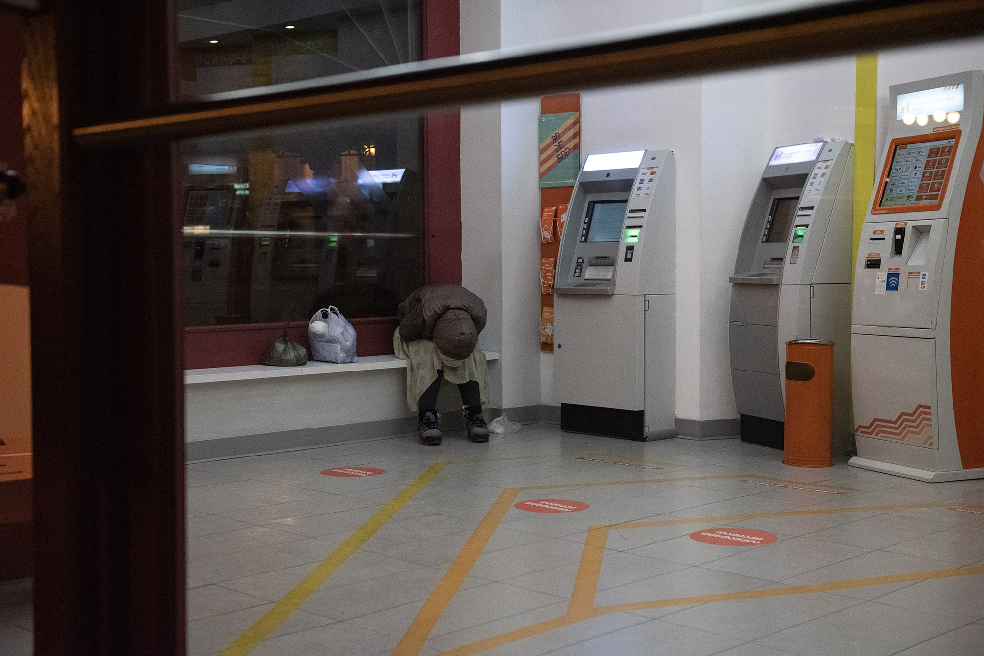 A woman sleeps inside a Bank of Georgia ATM area on 31 March. Photo: Mariam Nikuradze/OC Media.