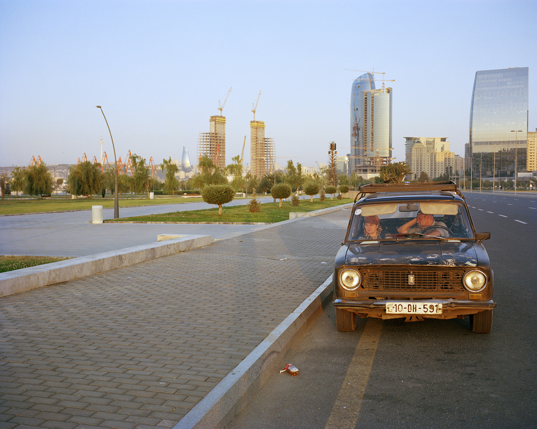 2016: A couple sits in an old Lada while Port Baku, a luxury shopping area is visible behind them; directly situated next to White City, an upmarket housing development. Its prices remain unattainable to most Bakuvians.