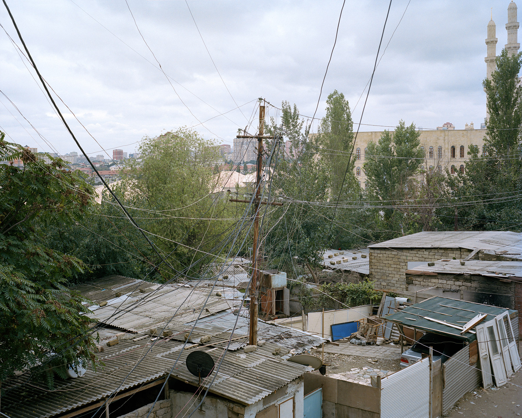 2017: The homes of internally displaced persons from Nagorno-Karabakh are illegally tapped into the city's electrical grid by a tangle of wires.  The homes are directly behind Heydar Aliyev Mosque, the largest mosque in the South Caucasus.