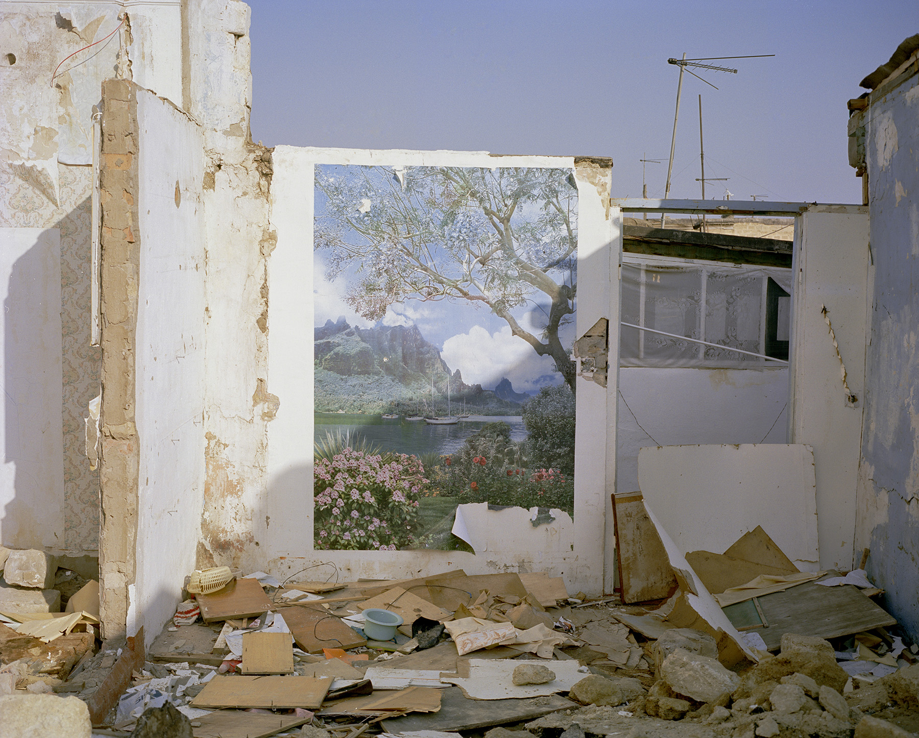2014: A poster depicting a scenic natural scene still hangs on the wall of a demolished home. – Sovietski, central Baku.