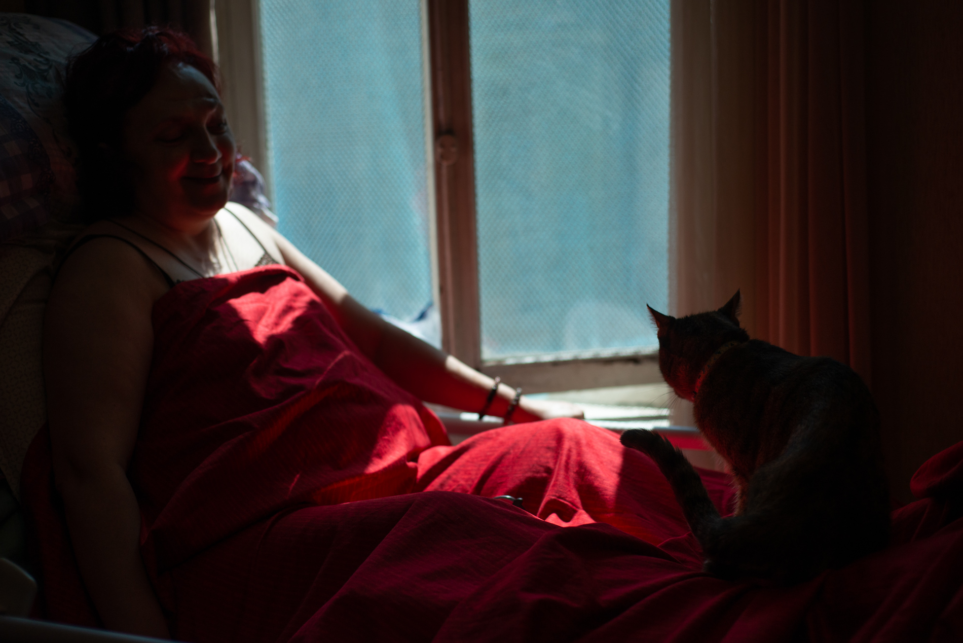 Inga spends a great deal of time in bed. Victoria, the family cat, is her permanent companion. Photo: Tamuna Chkareuli/OC Media.
