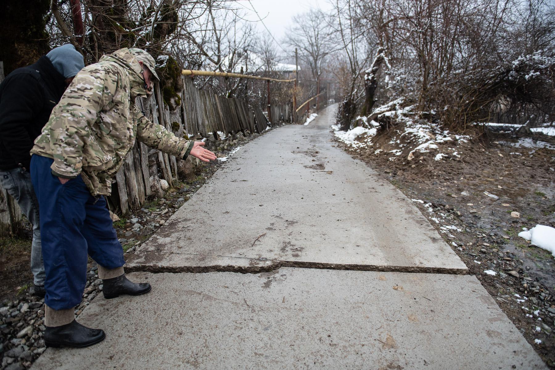 Shekiladze points at a newly built road that is already damaged. Photo: Mariam Nikuradze/OC Media.