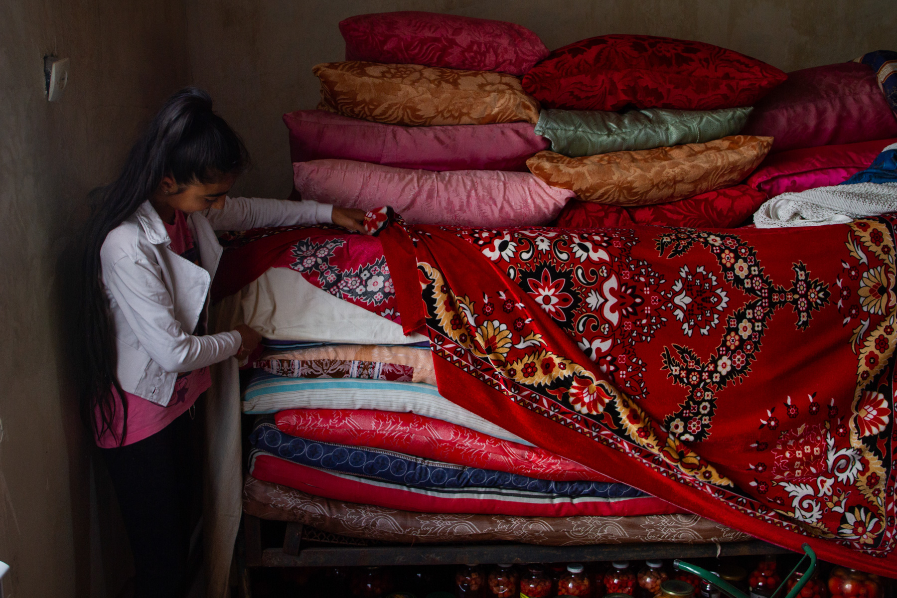 Maya shows off the traditional mattresses of their house, which Yazidi families are proud of. Photo: Hermine Virabian/OC Media.