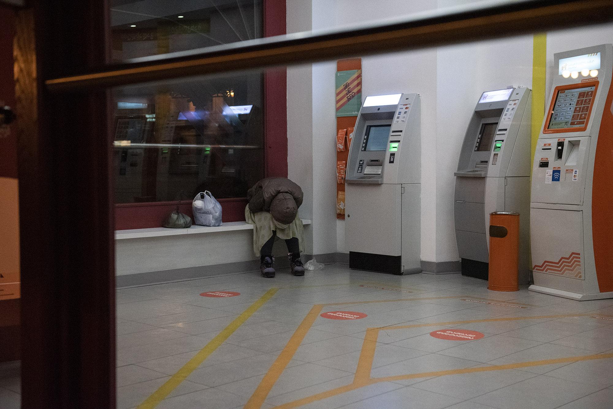 Женщина спит в отделении банкоматов Банка Грузии. Фото: Мариам Никурадзе/OC Media.