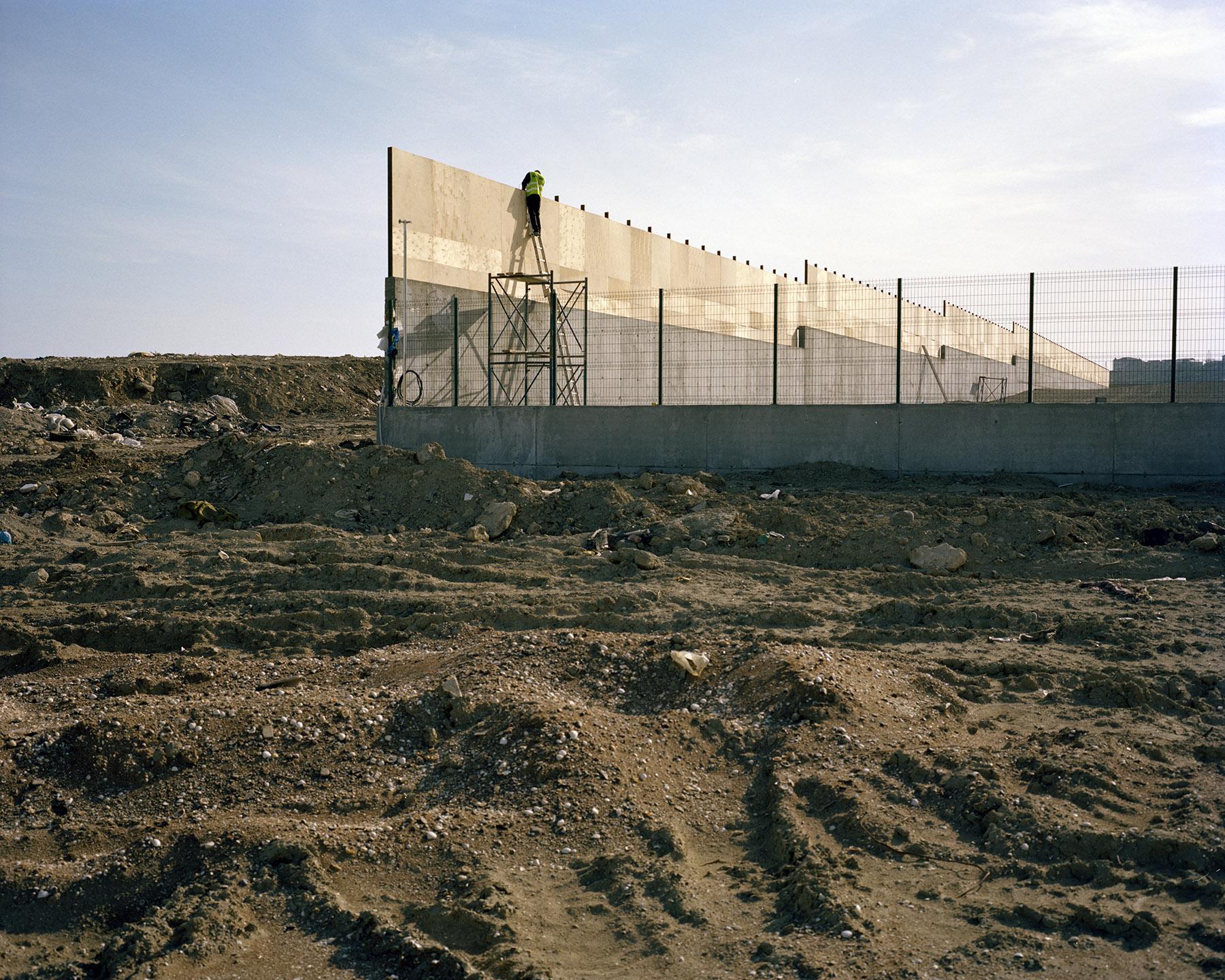 2015 год: Человек строит стену. Большие стены — обычное дело для Баку. Они часто не служат иной цели, кроме как скрыть менее «приятные достопримечательности» — ветхие дома бедняков или строящиеся районы.
