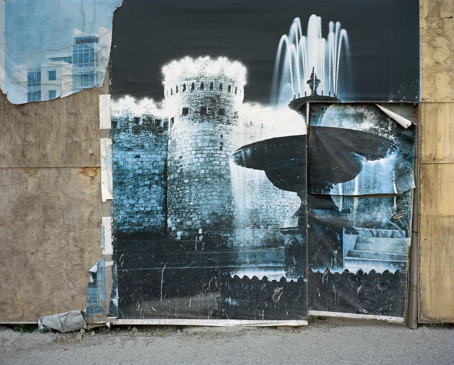 2015 год: Четырёхметровые высокие стены из песчаника простираются вдоль всех основных магистралей Баку и за его пределами. Между тем, недавно приобретённые участки или «большие перспективы» находятся под охраной или за оградами, обклеенными низкокачественной рекламой, изображающей достопримечательности страны — в данном случае — две гордости Баку: Девичью башню и близлежащие фонтаны.